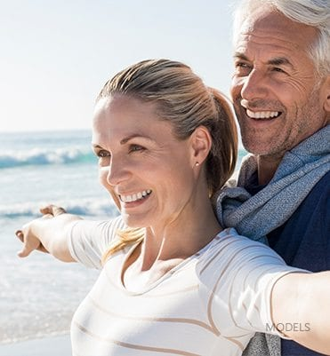 Mature Couple Smiling and Stretching at the Beach